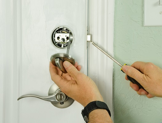 Closeup of a professional locksmith is installing or repairing a new deadbolt lock on a house exterior door with the inside internal parts of the lock visible.