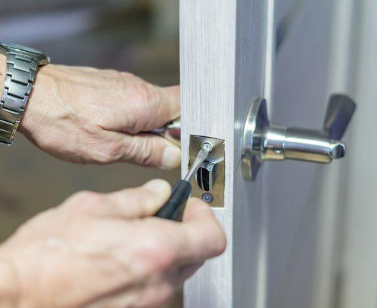 man repairing the doorknob with screwdriver. worker's hand installing new door locker
