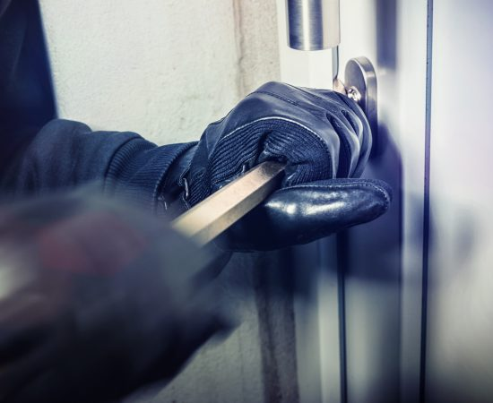 masked burglar with crowbar breaking and entering into a victim's home - shot with dramatic motion