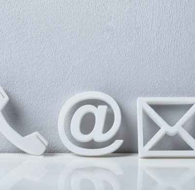 Contact Methods. Close-up Of A Phone, Email and Post Icons Leaning On White Wall
